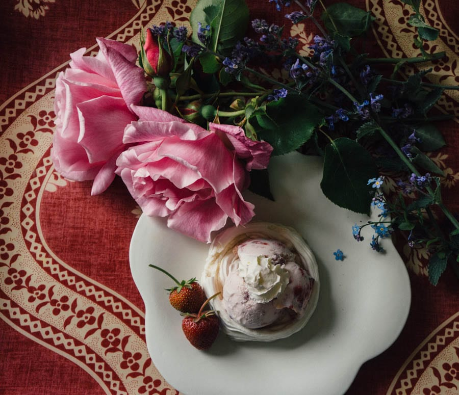 Meringue with strawberry ice cream and flowers on tray