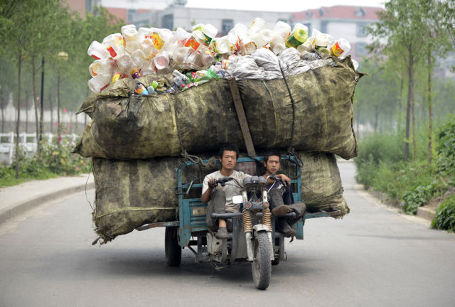 A motor tricycle loaded with recyclable plastic bottles drives along a street in Taiyuan