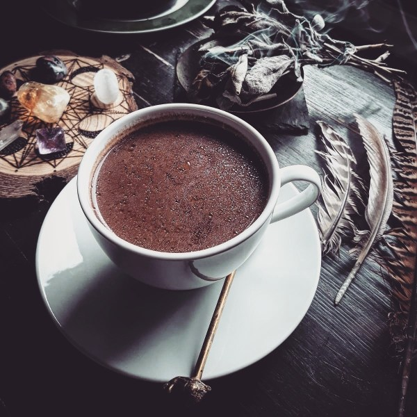 White cup and saucer filled with hot chocolate surrounded by crystals and feathers