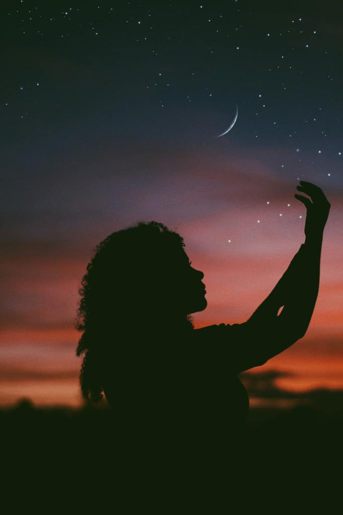 Long haired empowered female against a twilight sky