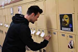 Sophomore Dylan Chitwood cracks a smile while placing positive sticky notes on students lockers November 12. Chitwood is a member of the FOR club and wrote many of the positive notes.