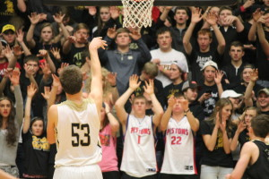 Alex Allen, #53, taking a free throw as the student body watches with arms raised.
