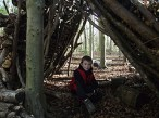 Sitting in his hand built shelter