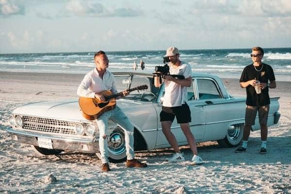three-men-near-white-sedan-on-shore
