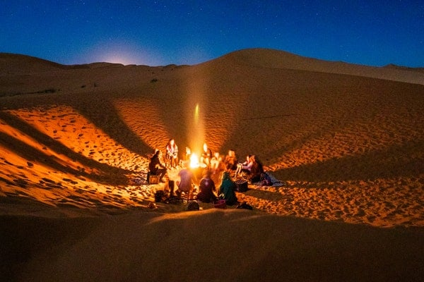 photo/people-sitting-in-front-of-bonfire-in-desert-during-nighttime