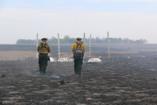 Burn Boss Blake Stewart/USFWS (left) and Firing Boss Nick Mink/BLM (right) walk out to the fire shelter test site after the fire has passed.