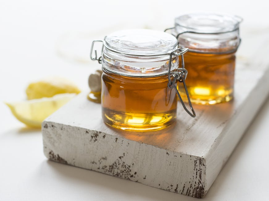 jars of honey on a wooden board