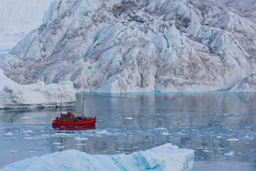 tourist boat in front of large iceberg
