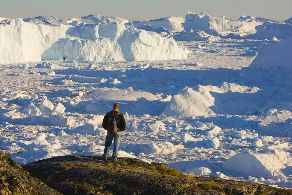 hiker overlooking fiord covered with small pieces of ice and large icebergs