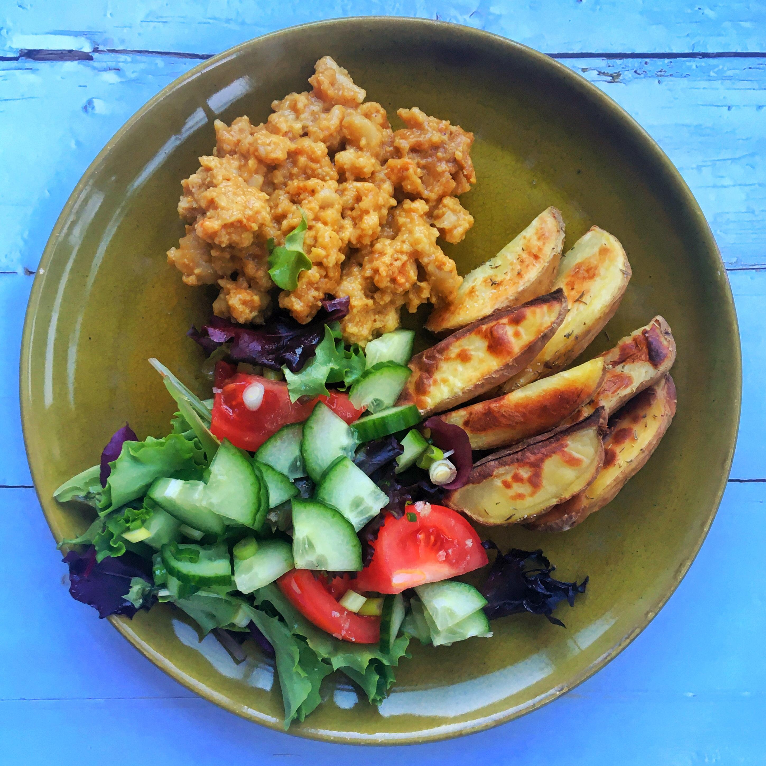 Zelfgemaakte seitan, gebakken aardappelen en een frisse salade