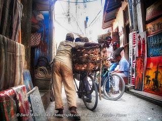 Man pushing bike through streets in stone town Zanzibar