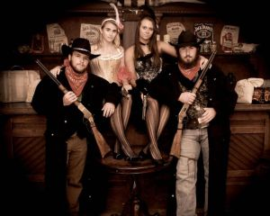 Two couples posing as cowboys and saloon gals for an old time photo.