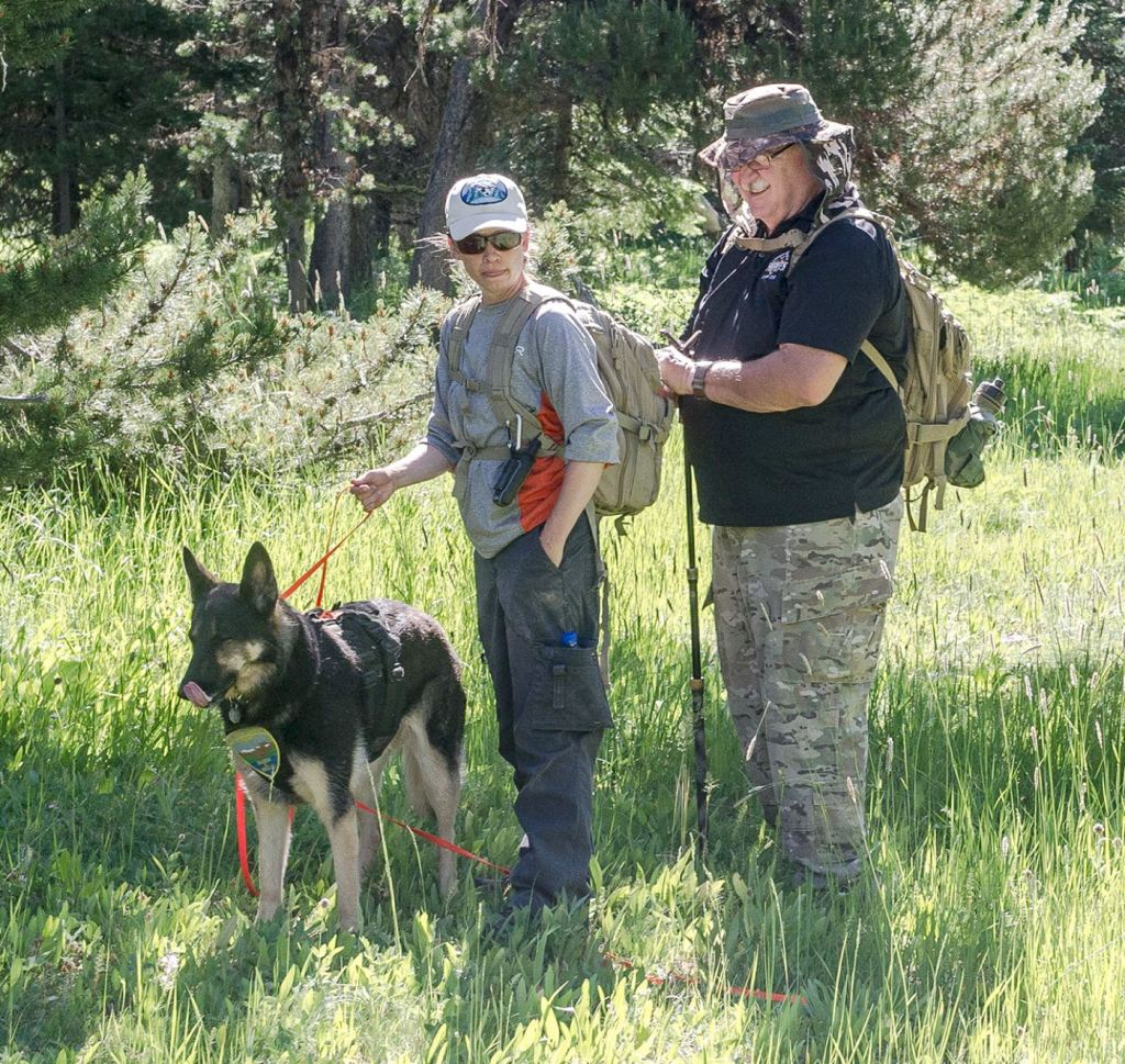 """Heather Howard and her dog Gracie work with Umatilla Sheriff's tracker Cliff Pease to plan the next step in tracking a """"lost"""" hiker on Sunday, June 27. Photo, Ellen Morris Bishop."""