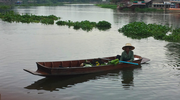 A Traditional Thai farmer selling vegetables along the river