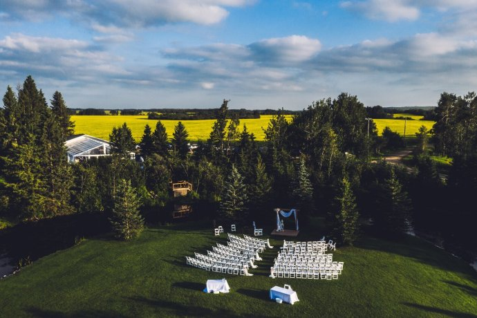 Birds eye view of intimate outdoor wedding venue surrounded by forest trees and fields