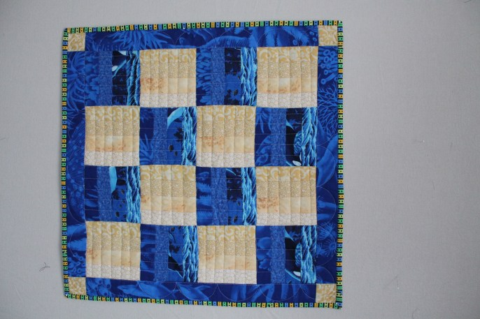 Free motion quilted in opposite direction of strips