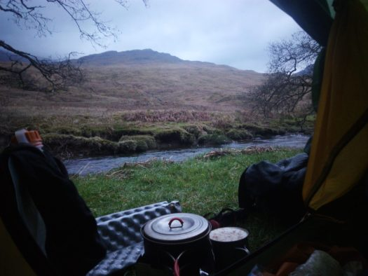 Wild camp in Scotland while walking the west highland way. Laid in tent with door open, heating water for breakfast and a coffee laid in tent