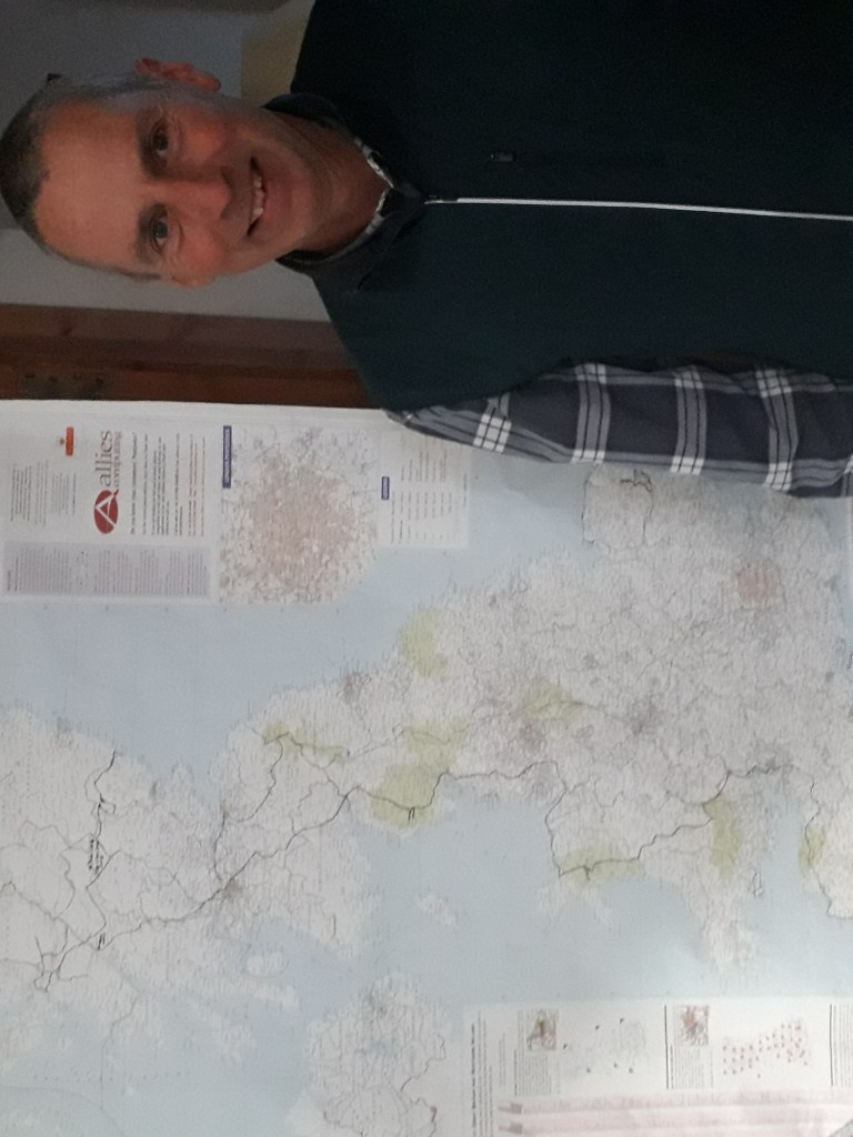 Mark standing next to a large-scale map of the UK
