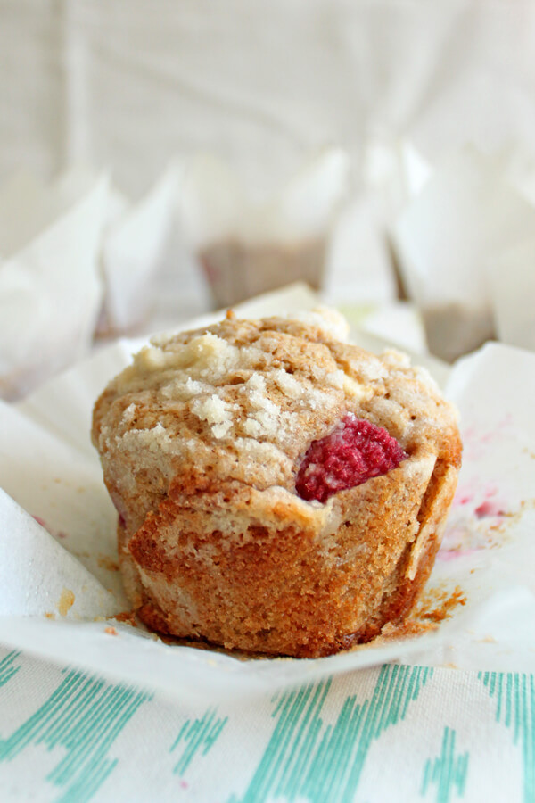 These Raspberry White Chocolate Chip Muffins are made with whole wheat flour. They are so soft and fluffy, and bursting with fresh raspberries! | wildwildwhisk.com