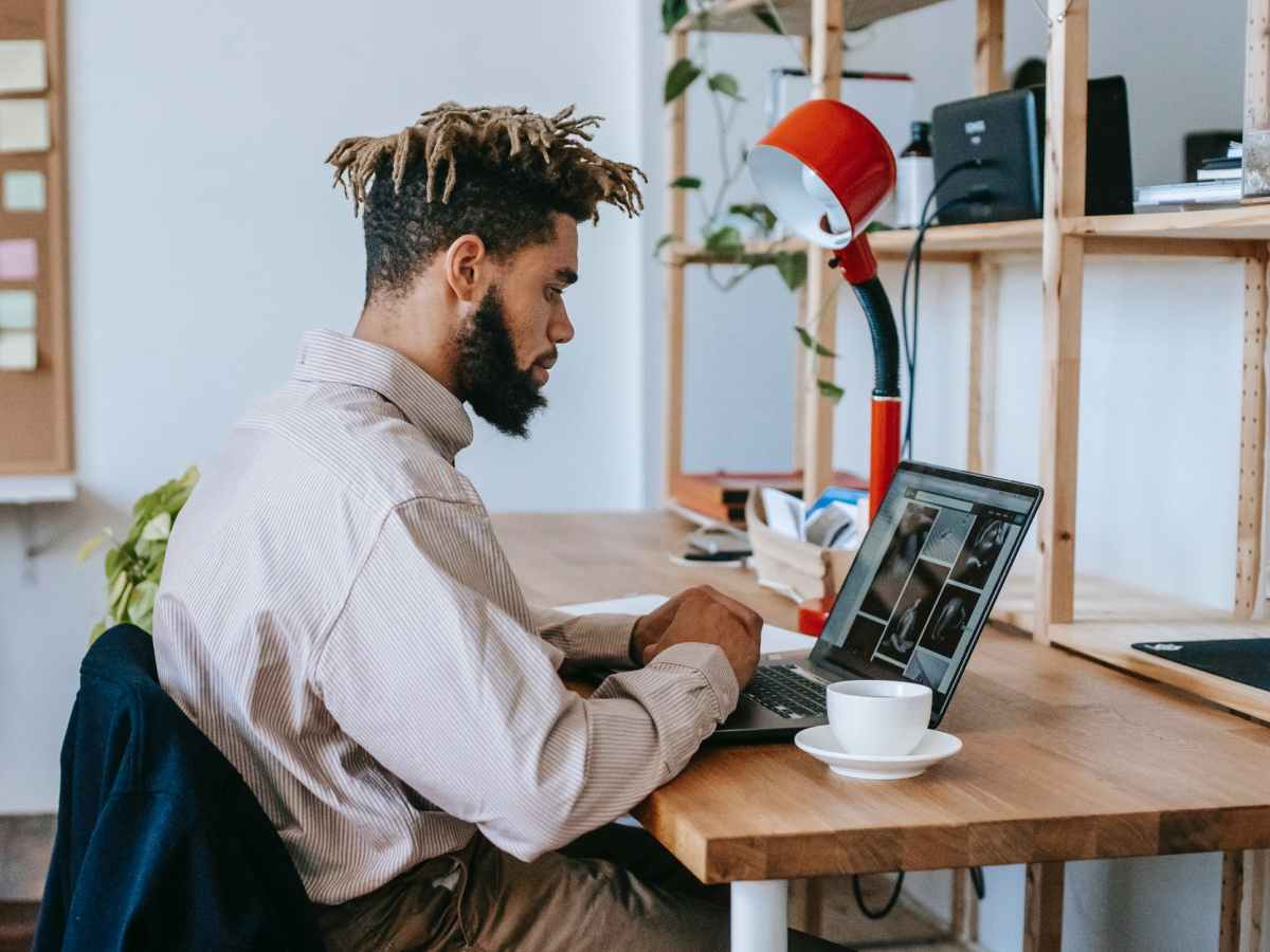 black man remote worker using computer in workplace