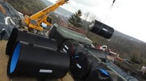 Kunststoffrohr wird per Kran in den Wasserspeicher eingesetzt