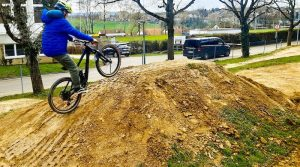 Junge fährt mit BMX-Rad Erdhügel hinauf