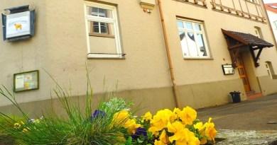 Eingang Lamm hinter Pflanztrog mit gelben Stiefmütterchen