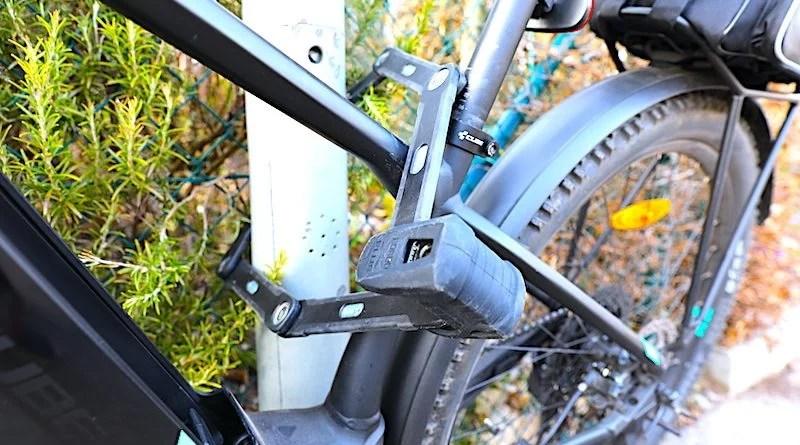 Fahrrad mit Faltschloss an Pfahl befestigt
