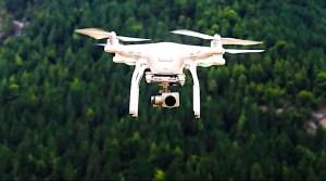 weiße Kameradrohne über einem Waldgebiet