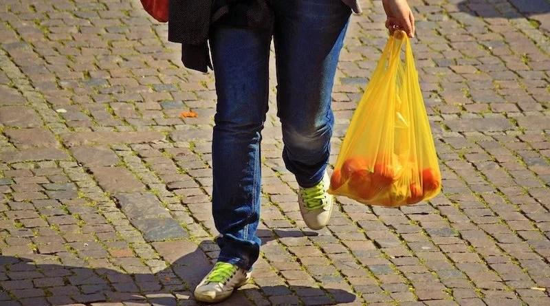 Fußgängerin in Jeans mit Tüte voller Orangen auf Kopfsteinpflaster