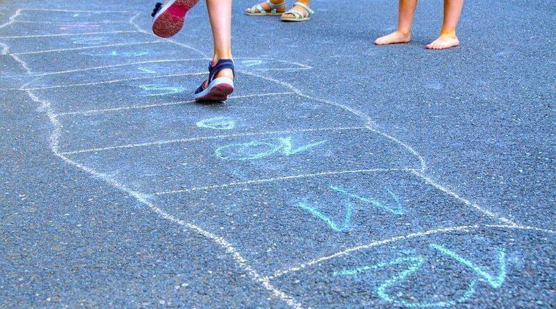 Kinder hüpfen auf Spielfeld auf der Straße
