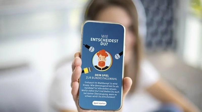 junge Frau zeigt App zum SWR-Onlinespiel für Erstwähler