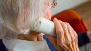 Alte Dame mit Telefonhörer in rechter Hand
