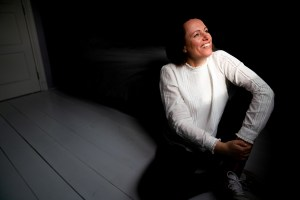 krachtige vrouw met gezicht in licht op zolderkamer