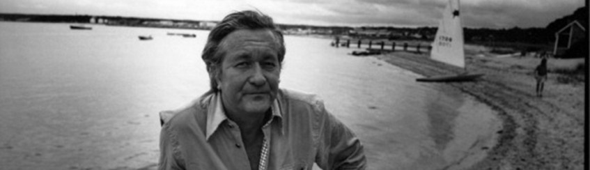 Image shows author William Styron facing the camera with a beach and boat in the background at sunset