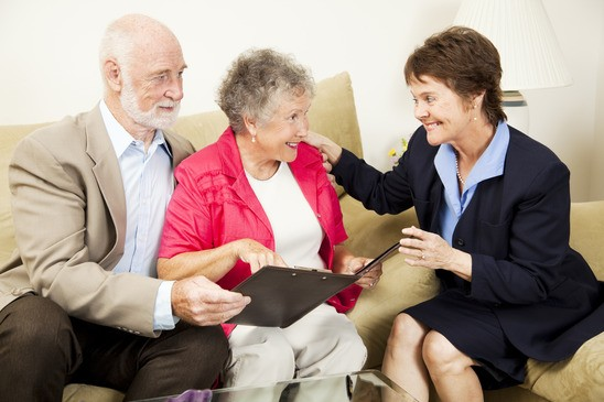 Sales woman making an aggressive pitch to a senior couple.