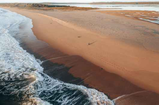 sandy beach with foamy waves