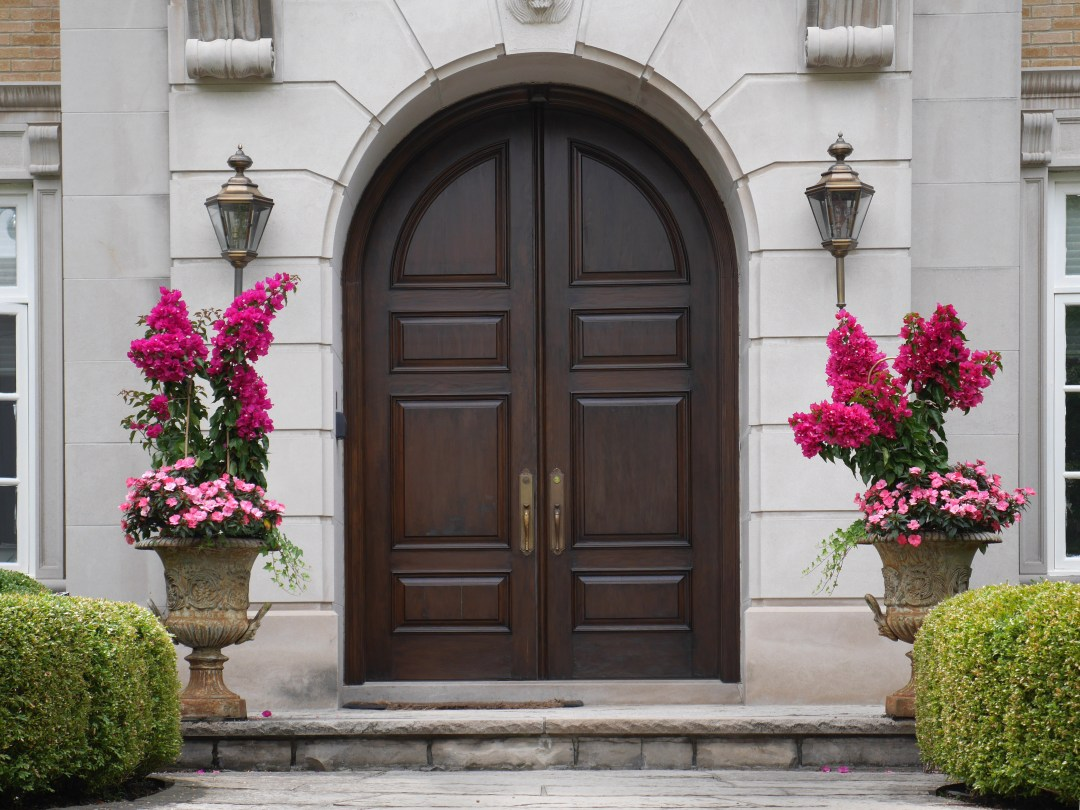 Dark solid wood double door with arched top