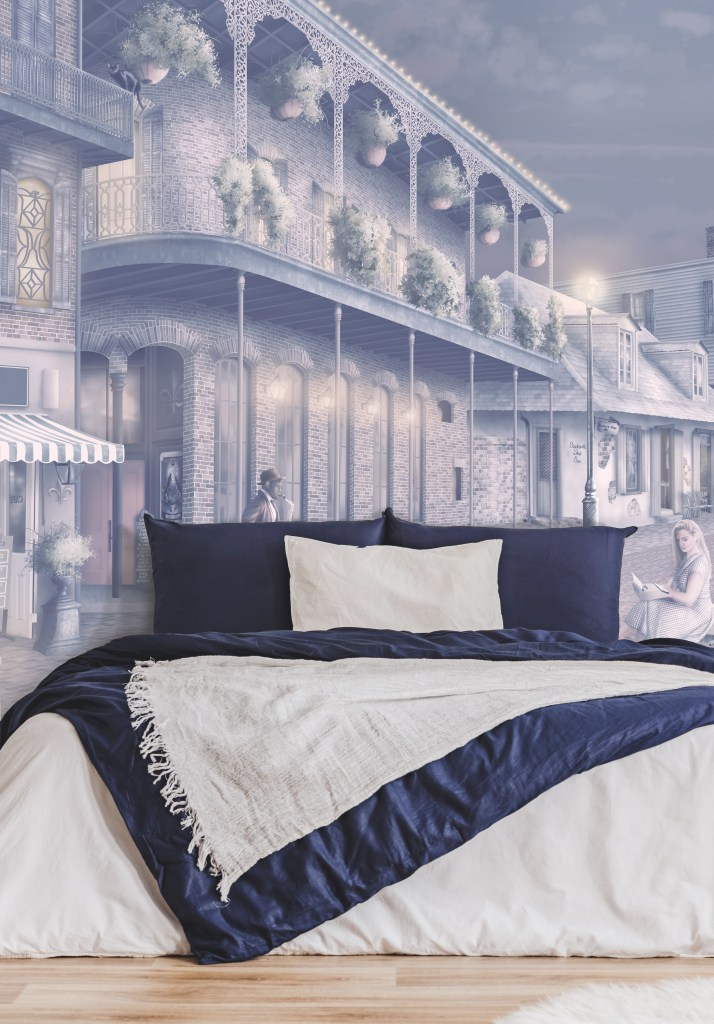 Custom wallpaper and murals Australia. Wallpaper in warm navy-blue, cream, beige, purple, pink. A romantic Wallpaper design set in the streets of New Orleans at night withs lights. Featuring musicians, voodoo art, cafes and more. Beige warm wood flooring, navy and white bed linen with white furniture. Amazing Statement Wallpaper Designs
