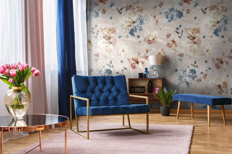 Interior decorating wallpaper designed to look like flowers falling into a pool of water. Its romantic and whimsical nature makes it a perfect wallpaper for nurseries, hallways, bedrooms and bathrooms.The warm rustic and earth tone colours in this design are by steel blue. Featured here in a living room with matching blue accent feature chairs, lilac rug, rose gold side table.
