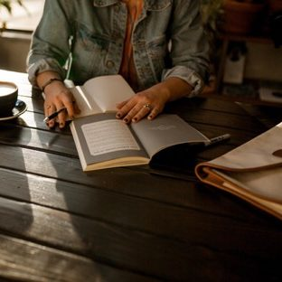 Photo of person in a green jacket looking at books on a wooden table | CBT for anxiety | Willow Counseling Nashville, TN 37212