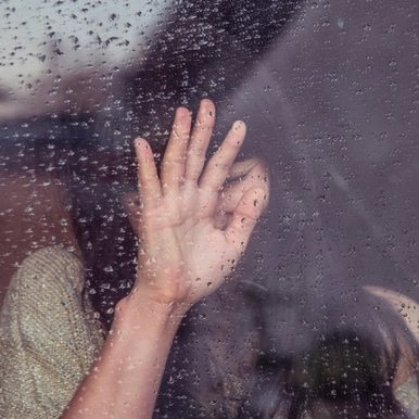 Adult woman with hand against rainy window, impacted by childhood trauma.