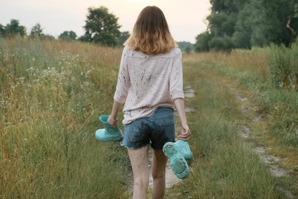 Photo of woman walking on rural road holding teal rain boots after going to counseling | Willow Counseling | Nashville, TN