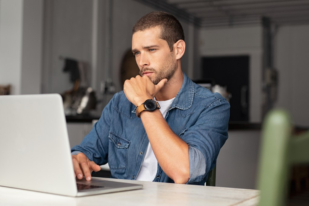 Young caucasian man working on laptop looking stressed | Signs of Burnout | Willow Counseling | 37212