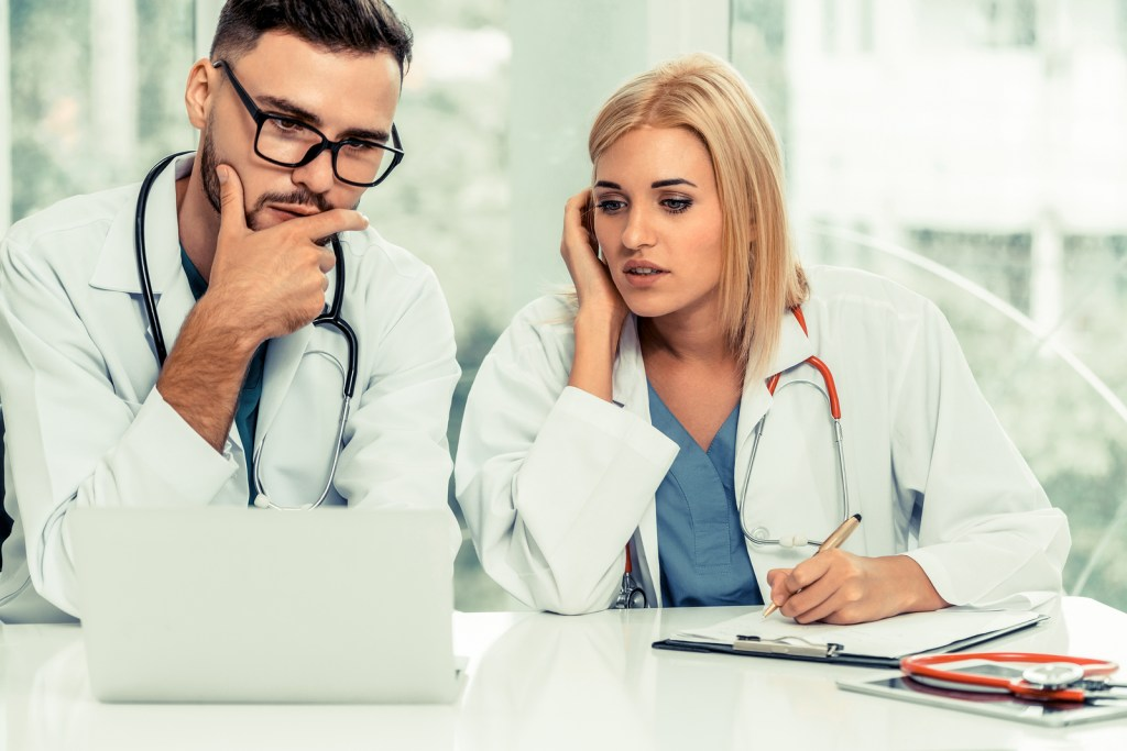 Two doctors consulting about a stressful, critically ill patient.  Our Nashville, TN therapists provide support and counseling to caregivers in the medical profession showing symptoms of burnout or needing therapy for stress.