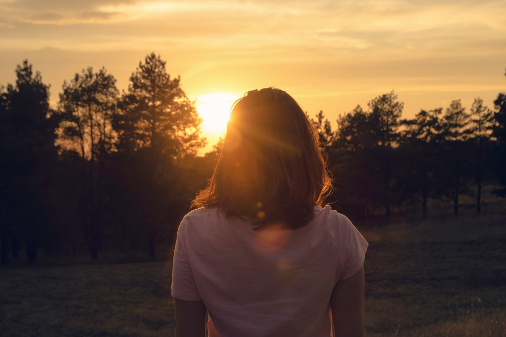 Woman in staring at trees during sunset after healing from sexual trauma| Healing from sexual trauma | Willow Counseling | 37212