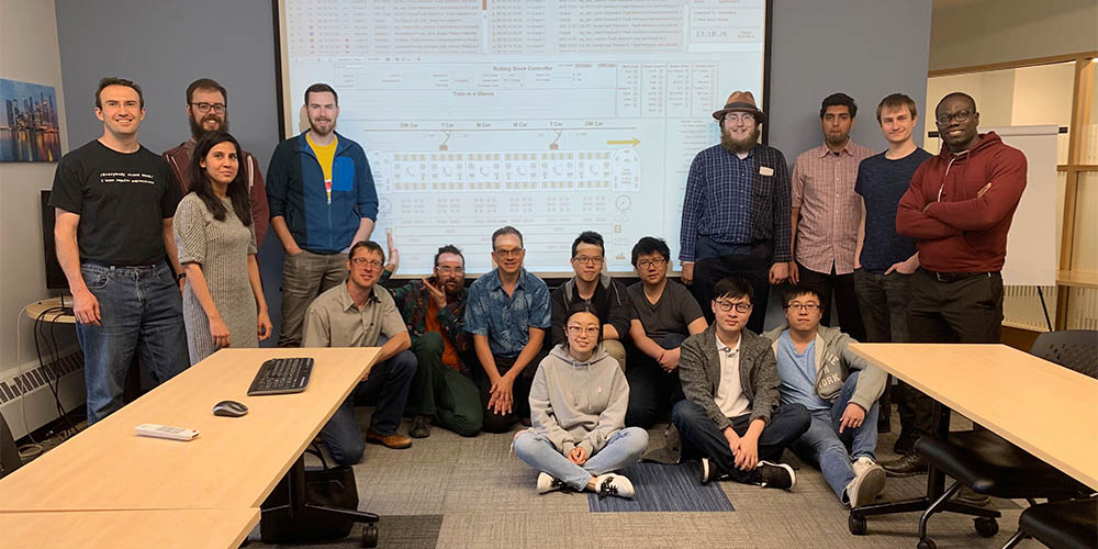 Willowglen employees standing in front of a screen projecting project work
