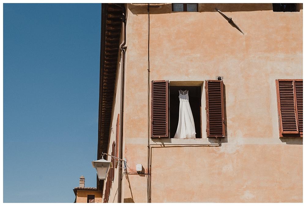 Wedding dress hanging in window of Villa Catignano