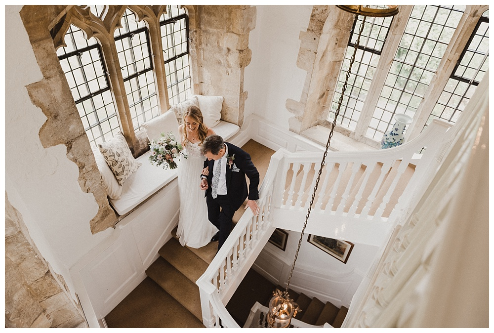 Bride and her father on the staircase at Butley Priory.