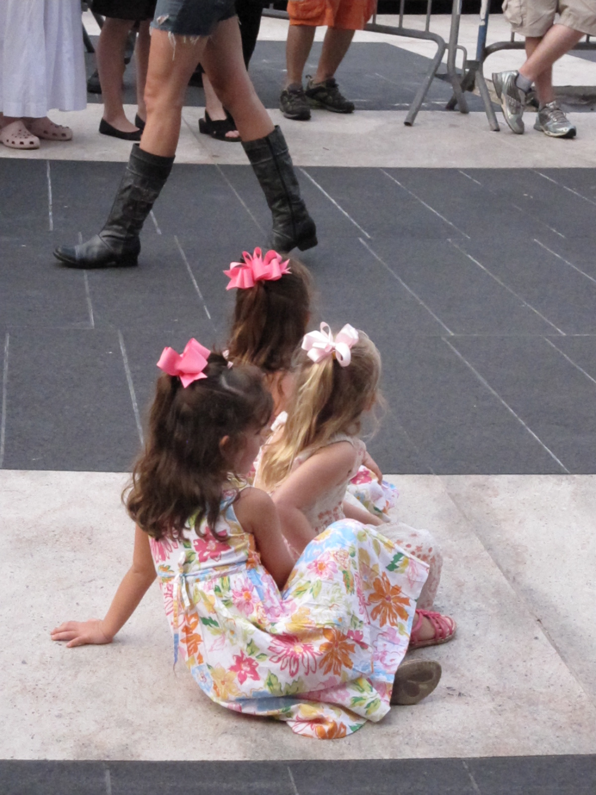 Three little girls sitting on Josie Robertson Plaza, mesmerized by Asphalt Orchestra.